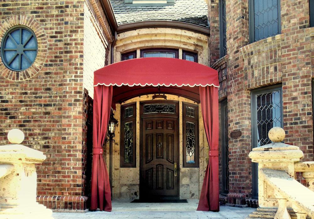 Capota estilo túnel en la entrada de una residencia, con cortinas.